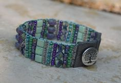 New summer design! Delicately hand-loomed bracelet featuring gorgeous shades of purple, lilac, violet and mint green! A true statement piece for