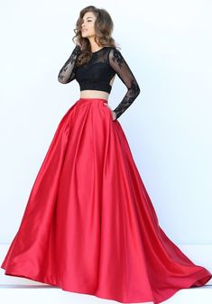 This Sherri Hill 50357 is a two-piece ballgown, composed of a long sleeve crop top with an exposed back, paired with a box-pleated skirt in pure color. The jewel neckline sits on a lace yoke, both framed with sheer lace long sleeves. Beneath the bare midriff, the two-pocket skirt billows with a sweep train.