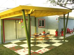 This oversized green-and-white checkerboard patio is the perfect canvas for the red handprints that adorn the outer edge, adding to the fun and retro feel of the backyard.
