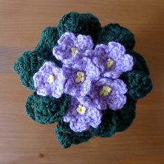 A crochet pattern that produces a display of African Violet flowers to be placed at the top of a flower pot.