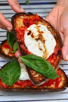 Hand holding a mozzarella bruschetta Tomato Bruschetta, Tomato Mozzarella, Caprese Salad, Authentic Italian Pizza, Sandwiches, Classic Salad, Bread Alternatives, Balsamic Reduction, Pasta