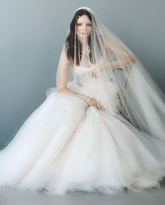 """Both this airy ball gown and lavish cathedral veil are embellished with scattered opalescent crystals for a light-reflecting ensemble that sparkles, glows, and bewitches.The Details: Monique Lhuillier """"Brilliance"""" veil, $3,400, ball gown, $16,000, and capelet, $3,320, moniquelhuillier.com. Solange Azagury-Partridge cuff, price upon request, 212-879-9100. De Beers ring, price upon request, debeers.com.Styled by John Paul Tran. Market work by Colleen Banks and Carrie Goldberg. Make..."""