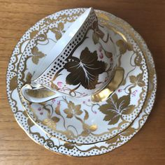 Royal Chelsea Vintage Teacup Trio This is a stunning teacup, saucer and matching side plate! This set has large and small gold leaves and twisty vines with hand painted pink berries. The outside edge of all the pieces has a gold polka dot border. The cups foot and handle are also trimmed