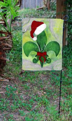 "Santa Christmas fleur de lis garden flag from my art. Flag is double sided and measures approximately 13.5 "" x 18.5"". Stain and water resistant. My art print is permanently applied by dye sublimation."