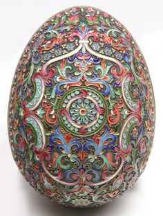 A Russian champlevé Easter egg, Moscow circa 1908 - 1917. The two halves with a gold washed interior, the exterior profusely decorated with flat beaded borders, trefoil borders, foliate scrolls, flower heads, brackets, scrolls and a central roundel all in subtle complimentary colors against an oxidized silver ground. Hallmarks inside the lower half for Pavel Ovchinnikov, Moscow kokoshnik 84 standard. Sells March 19, 2015.