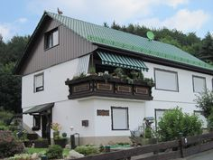 """Wohnhaus mit bepflanztem Holz-Balkon. Grüne Steildacheindeckung inkl. Schneefang und Dachschmuck """"Hahn"""" vom Dachdeckermeister Helmut Mai GmbH in Bad Emstal (34308)   Dachdecker.com"""