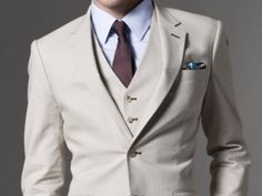 A cream colored three-piece suit. Soft blue dress shirt. Maroon tie. Subtle turquoise pocket square. Pure class, and the perfect look for summer. This suit's color doesn't absorb the sun's rays as much. You'll feel cool and look cool at the same time.