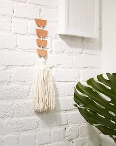 Seeking an alternative to your standard prints and paintings? This minimalist wall hanging, created using air-dry terracotta clay and handspun yarn, will add a unique touch.