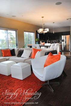 Simply Stunning Spaces Living Room Design. We absolutely love these orange accents in this Hillcrest bachelor pad. They add the perfect amount of brightness and positivity to the dark wood floors and brown accents on the white couch. Talk about living room dreams! For more interior design inspiration visit: www.simplystunningspaces.com
