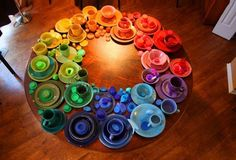 These are all my dishes, that I buy at thrift stores, arranged into a color wheel on my kitchen table.