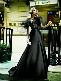 Young Woman Wearing a Basic Black Evening Gown w. a Sleek Cinched Waist Beltline @ a Bodice Constructed Top w. Chiffon Ruffle Shoulder Straps.
