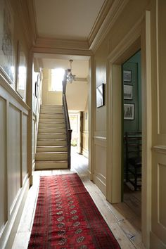 Earthy beige brings out the shadows in generous molding, light-wood floors, and aged stair treads. Farrow & Ball's Cord.