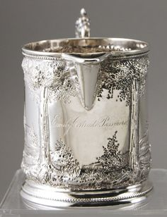 "American Coin Silver W. I. Tenney - NY 19C Repousee Pitcher. The William Ingalls Tenney (1806-1848) coin silver pitcher, has elaborate chased and repousse landscape scenes. There is a period script monogram on the front, ""Emily Gertrude Passmore"" . Hallmarked on the bottom Tenney 251 B.Way. In good condition. Measures 3 1/2"" high and 5 1/2"" from spout to end of handle. Weighs 5.1 troy ounces."