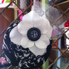 Rolled bandana flower with button, flower & tulle accents. This is a clip that can be worn by itself, in a group of clips or on a headband. From infants (on a headband) to adults.