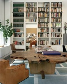 Diane von Furstenberg home - Cascading white book shelves with a dark-brown natural wood coffee table.