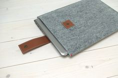 Felt case for Macbook Air and Pro 13 inch with leather closure. Sleek 13 laptop sleeve with a small red detail. Made of 3mm thick undyed wool felt in Grey, Black or Sand brown. The matte and non-varnished leather waterbuffalo leather closure will age nicely in time. The (dark) brass