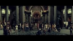 """The arrangement of the people with the architecture in the background makes the video look like an urban recreation of the famous """"School of Athens"""" painting which depicted pretty much every great philosopher of that era i.e. Plato, Socrates & Aristotle. But in this video the people are on the grind for cash and predatory towards each other (the shark). So maybe this is partly a comment on the type of people society idolizes in the past v. present."""