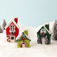 "Very Merry Village. Start with a plain papier-mache house ornament (available at crafts stores), remove the hanger, & paint the sides and chimney a desired color. Let the first coat dry & apply another coat if needed; let dry. Paint the chimney top, roof, windows, door, and base white. Once all the paint is dry, glue miniature trims into place. To finish, brush glue over the areas you want covered with ""snow"" and sprinkle with glitter. Let the glue dry and shake off excess glitter."