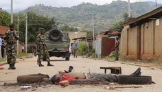 Soldiers stand near the body of a man who was burned alive by protesters in Burundi's capital Bujumbura, May 7, 2015. Protesters burned the man alive on Thursday, saying he was a member of the Imbonerakure youth wing of the ruling CNDD-FDD party which had attacked them during their demonstrations against Burundian President Pierre Nkurunziza's bid for a third term, a witness said. REUTERS/Jean Pierre Aime Harerimana