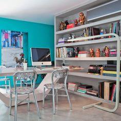 Quer ter uma biblioteca em casa? Se inspire nesse ambiente, com livros e objetos de arte na estante e mesa de cimento que serve pra trabalhar e pra jantar.