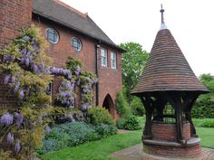 On the east front of Red House grows a lilac-coloured wisteria.  The freestanding well is to the right.  Red House is the Bexleyheath home built for William Morris by architect Philip Webb in 1859.