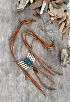 This pretty Breastplate inspired by Native american, will hypnotise you thanks to its beautiful chrysocolle !  The neck is composed of cow dark Brown leather, bronze beads and apprêts, chain with a boho clasp, the necklace ends with some feathers in the back. The breastplate is composed of bronze beads, bone hairpipe and chrysocolle gemstone beads. Some fringes ends the breastplate with bronze beads, and a eye of tiger arrow graved and paint by hand. The necklace is 68 cm(26.7 inches) long…