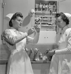 "November ""Nurses in training. Babies' Hospital, New York. A graduate nurse (right) watches student Susan Petty prepare a hypodermic for a patient. Strict adherence to doctors' orders is something every probationer must learn."