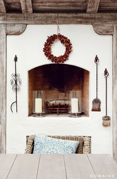 Living room fireplace with wreath and thick, white candles