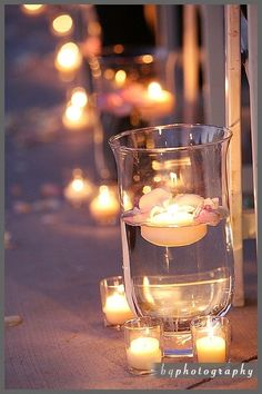 Hurricane vases down the aisle with floating candles and flowers