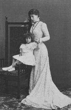 Victoria Melita, Grã-duquesa de Hesse, está olhando para a filha, a Princesa Elizabeth, que está sentada no braço de uma cadeira olhando para frente. A Grã-duquesa segura a mão esquerda de sua filha. Em 1898.