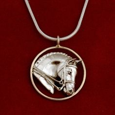 """This sterling silver Dressage horse head comes in a 1"""" diameter 14k gold circle. Available in 16"""", 18"""", or 20"""" sterling silver snake chain with lobster clasp closure. Perfect for the Dressage enthusiast!"""