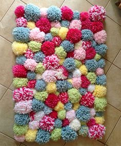 make up a batch of colourful pom-poms and attach these onto a woven mat.