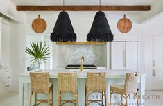 ASHLEY GILBREATH INTERIOR DESIGN: Paneled appliances and brass pulls give this Rosemary Beach kitchen a sleek look. A honeydew green island adds a pop of color, and woven shade pendants with raffia fringe add texture to the space. An iridescent backsplash is the icing on the cake!
