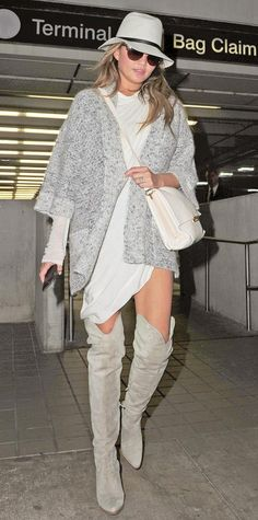 Chrissy Teigen mastered tricky in-between weather by pairing her draped LWD with an oversize slouchy gray knit, a gray felt wool hat, a cross-body holdall, and over-the-knee dove gray boots.
