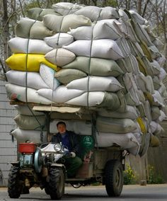 A woman rides a tricycle carrying polystyrene boxes in Shanghai, China.  Picture: China Foto Press / Barcroft Media