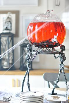 A fun pumpkin dispenser makes such a great statement over these metal skeletons. More Halloween party ideas on the post.