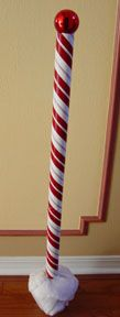 DIY North Pole sign: Wrapping paper Red Plastic or styrofoam ball painted red Cardboard tube from wrapping paper Flower Pot Floral foam Christmas drape Hot glue decorative ribbon