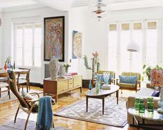 """Add an assortment of vases and decorative pillows to a Mid Century room to create a more personal look that doesn't feel """"bare bones"""". Colorful prints and abstract art add color to white walls and help to carry the eye across the room."""