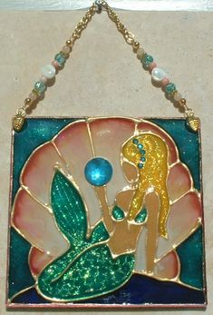Blonde Mermaid Beach Art Wall Jewelry Stained Glass Ornament, Wall Hanging and Suncatcher. Handmade Beach Kitchen Artwork with gemstones, crystals and gold plated chain and embellishments. Stained glass art hand painted on textured art glass for home, kitchen and bathroom coastal sea side theme decor. Decorative creative artwork made by Pat Desmarais in the USA on Etsy, $30.00