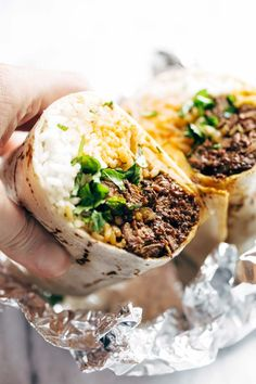 Korean BBQ Burrito - an easy food-truck-style recipe you can make with a slow cooker! spicy beef, kimchi, rice, cilantro, and sriracha mayo in a soft flour tortilla. | pinchofyum.com