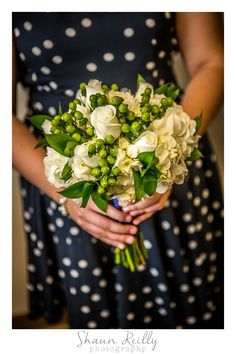 Bridesmaid's bouquet of white flowers with green berries.