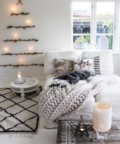 Weihnachtliche Dekoidee -Zweige als Tannenbaum an der Wand angeordnet