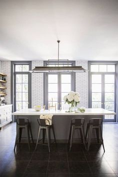 Large windows and doors in kitchen. Love this huge island and light fixture.