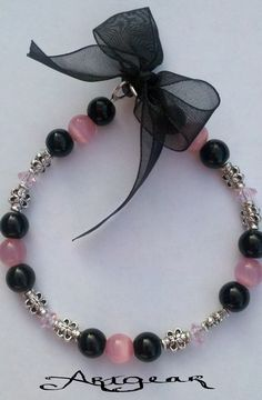 Cats eye pink and black beads. Adjustable with a black bow. $10.00