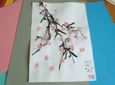 Chinese New Year Crafts for Kids use straws to blow the brown or black water color and then add blossoms