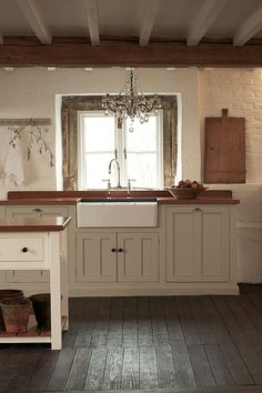 A rustic kitchen with a crystal chandelier. deVOL Kitchens