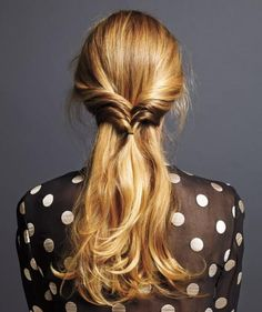 To get this look: Center-part your hair and pull back a narrow section from each temple to the nape. Then, secure with an elastic hairband. Flip the tail inward, through the V formed by the two strands—Topsy Tail–style. Repeat directly below with two more pairs of strands; secure and flip each pair.