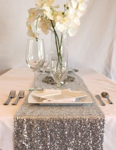 Silver Sequin Table Runner.  Add some glam to your glitter wedding with sequin table covers from Afloral.com.  Complete this look with high-quality faux orchids and cheap glass vases, all from Afloral.com. Gorgeous table runner in shining silver with silver sequins.  A great accent to make your wedding displays and photo shoots sparkle!