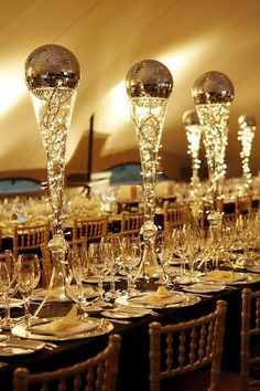 Opulent gold-themed party... Centerpieces adorning the tables are tall clear glass flutes filled with mini lights and topped with small gold disco balls.