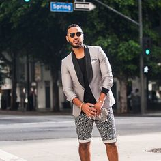 Shop this look on Lookastic:  http://lookastic.com/men/looks/blazer-long-sleeve-t-shirt-shorts-sunglasses-bracelet/11486  — Dark Brown Sunglasses  — Grey Blazer  — Black Long Sleeve T-Shirt  — Gold Bracelet  — Black and White Geometric Shorts